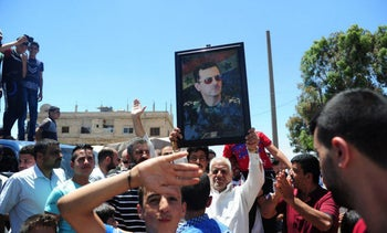 Residents celebrate the army's arrival in the formerly rebel-held town of Ibta, northeast of Deraa city, Syria in this handout released on June 29, 2018