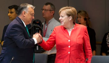 Hungarian Prime Minister Viktor Orban, left, greeting German Chancellor Angela Merkel during a breakfast meeting at an EU summit in Brussels, June 29, 2018.