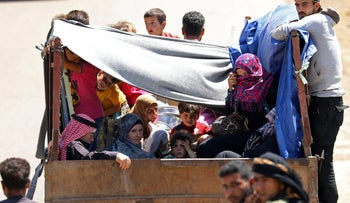 Internally displaced people from Deraa province ride on a back of a truck near the Israeli-occupied Golan Heights in Quneitra, Syria June 30, 2018
