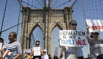 Demonstrators carry signs while marching across the Brooklyn Bridge during a protest against the Trump administration's policy on separating immigrant families in the Brooklyn borough of New York, U.S., on Sunday, June 30, 2018