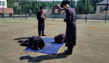 Hasids pray at the site of the Rebbe's grave in Poland