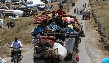 Internally displaced people from Daraa province sit on a truck loaded with belongings near the Israeli-occupied Golan Heights in Quneitra, Syria, June 30, 2018.
