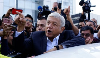 Presidential candidate Andres Manuel Lopez Obrador is surrounded by members of the media as he departs after casting his ballot at a polling station during the presidential election in Mexico City, Mexico, July 1, 2018.