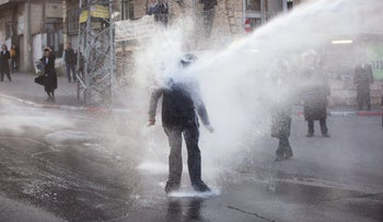 An ultra-Orthodox Jew getting hit by a police water canon during a protest against Israeli army conscription, in Jerusalem, March 2017.