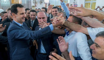 Syrian President Bashar Assad, left, greeting Syrians following the prayers of the first day of Eid al-Fitr, in Tartous, Syria, June 15, 2018.