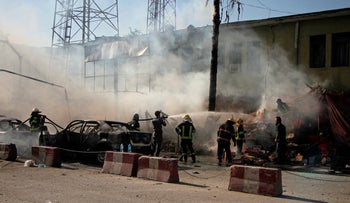 Police and firemen work at the site of a deadly suicide attack in Jalalabad, Afghanistan Sunday, July 1, 2018