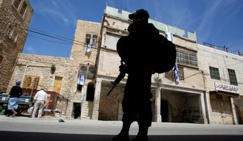An Israel Defense Forces soldier patrols near the house of Jewish settlers in Hebron, in the West Bank, March 27, 2018.