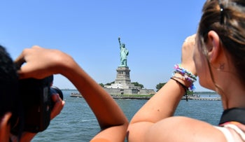 People take photos of the Statue of Liberty from the ferry to Liberty Island on July 2, 2018 in New York City.