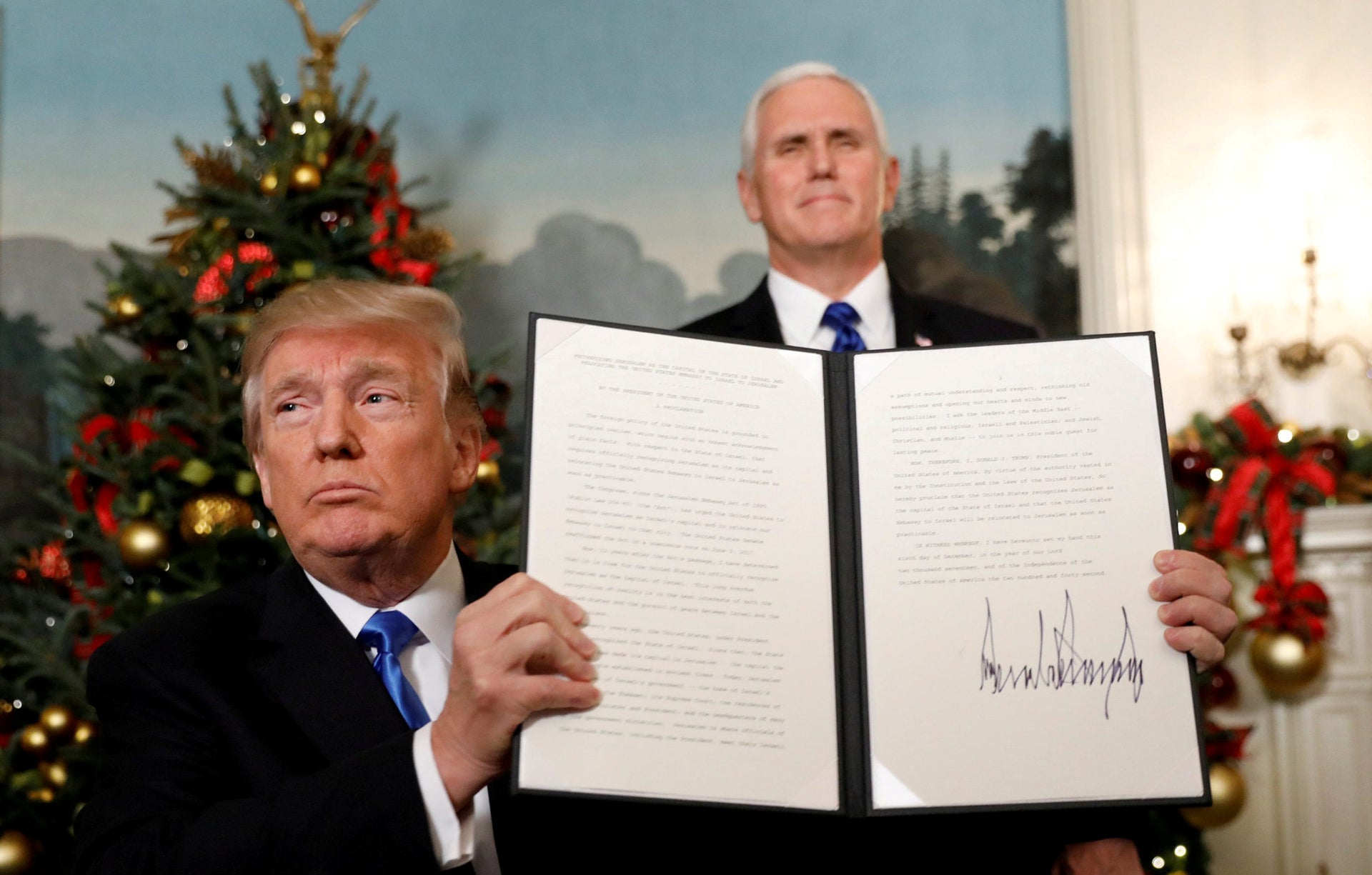 U.S. Vice President Mike Pence stands behind as U.S. President Donald Trump shows the proclamation he signed that the U.S. recognizes Jerusalem as the capital of Israel, December 6, 2017