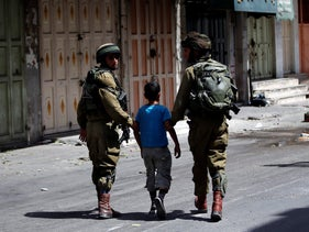 File photo: Israeli soldiers detaining a Palestinian child in Hebron, 2014
