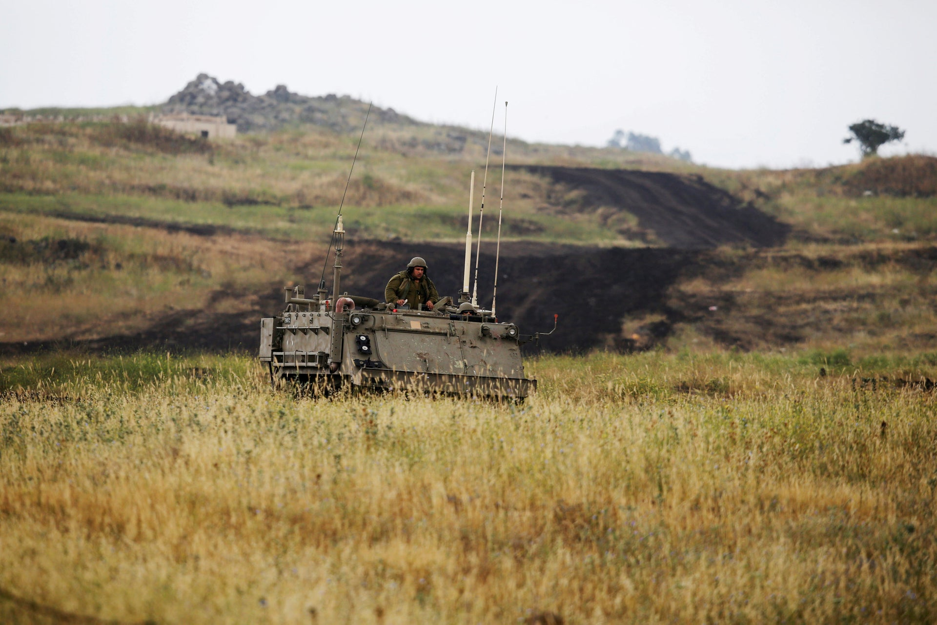 An Israeli soldier sits on an APC as it drives near the Israeli side of the border with Syria, May 9, 2018.