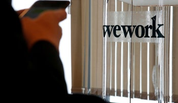 FILE PHOTO: A guest attends the opening ceremony of WeWork Hong Kong flagship location in Hong Kong, China February 23, 2017.