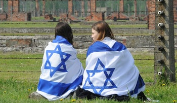Two teens on a school trip to Poland are sitting at the Auschwitz-Birkenau concentration camp wrapped in Israeli flags.