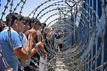 Displaced Syrian youth clutch the barbed-wire fence along the border with the Israeli-annexed Golan Heights calling for international protection. July 4, 2018.