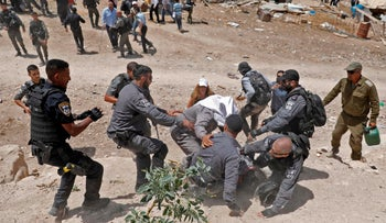 Israeli security forces arrest a demonstrator protesting against demolitions in the Palestinian Bedouin village of Khan al-Ahmar, east of Jerusalem in the occupied West Bank on July 4, 2018