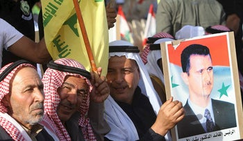 Hezbollah supporters hold a picture of Syrian President Bashar Assad as they listen to Hezbollah leader Sheik Hassan Nasrallah, who delivers a speech through a giant TV screen from a secret place, during a rally to mark al-Quds (Jerusalem) Day, at the village of Maroun el-Rass on the Lebanon-Israel border, south Lebanon, Friday, June 8, 2018