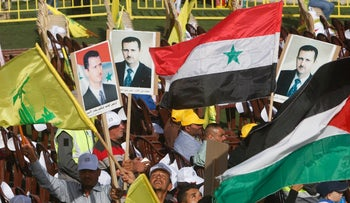 Supporters of Lebanon's Hezbollah carry flags and pictures of Syria's President Bashar Assad in southern Lebanon June 8, 2018