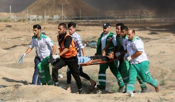 Palestinian paramedics carry a wounded protester away from the scene of clashes with Israeli forces during a weekly demonstration on July 6, 2018.