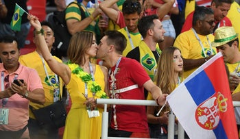 Fans from Brazil and Serbia share a kiss during their national teams' World Cup game.