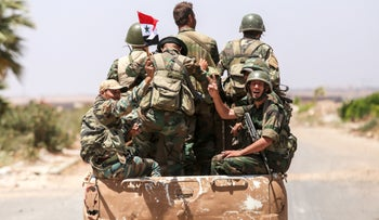 Syrian soldiers riding in the back of a pickup truck at the Nassib border crossing with Jordan. southern province of Daraa, July 7, 2018.