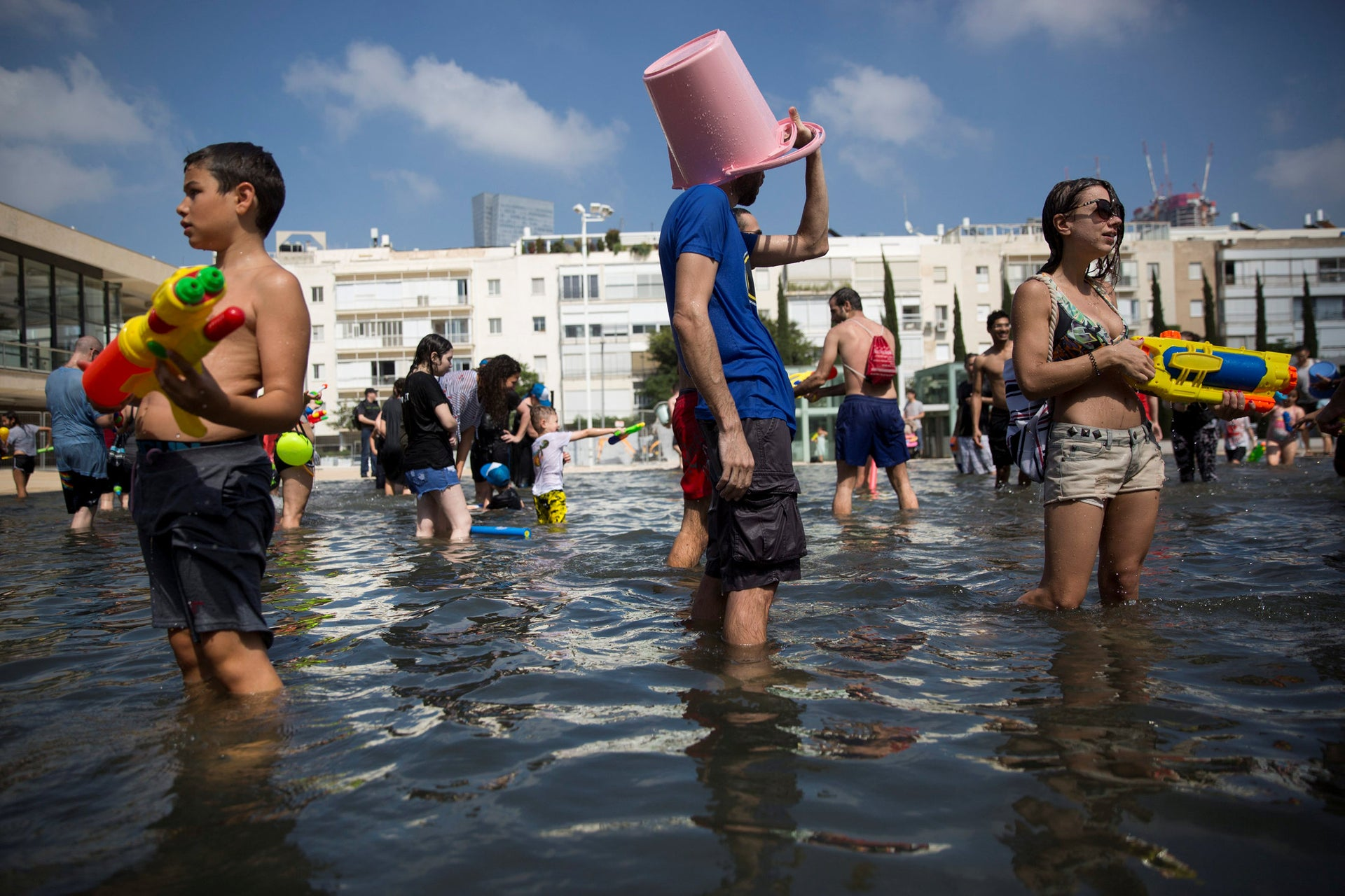 A man covers his head with a bucket during a water fight cub event attended by several hundred people, and held annually to mark the start of the summer vacation, at Habima Square, in central Tel Aviv, Israel, Friday, July 6, 2018.