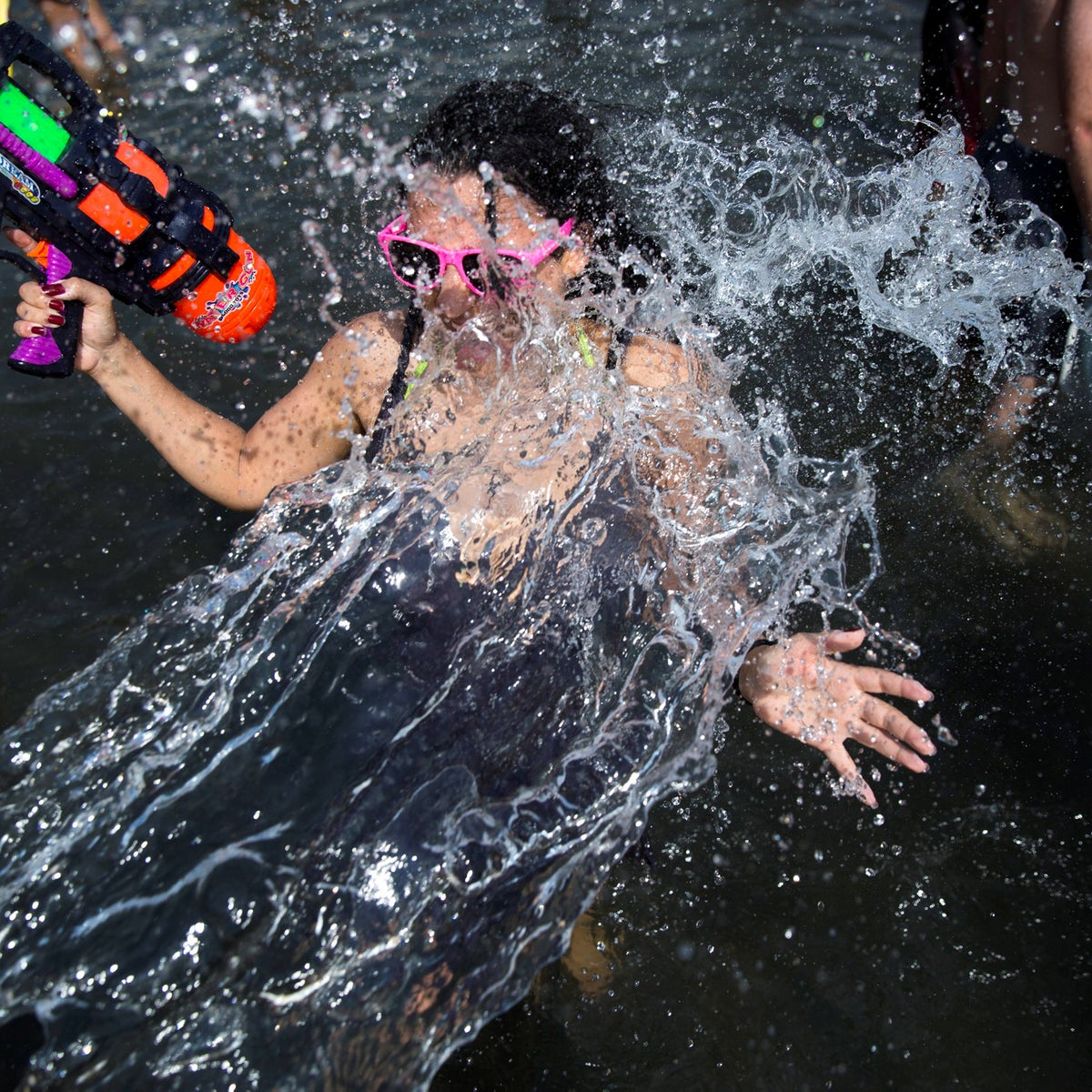 People spray water during a water fight cub event attended by several hundred people, and held annually to mark the start of the summer vacation, at Habima Square, in central Tel Aviv, Israel, Friday, July 6, 2018.