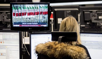 Television screen shows a news report on the lifting of Iran's sanctions as a financial trader monitors data at the Frankfurt Stock Exchange in Germany, 2016.