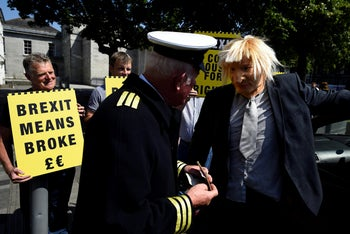 A man wearing a Boris Johnson mask has his British passport taken off him during a 'Borders Against Brexit' protest in Dundalk, Ireland, June 28, 2018.