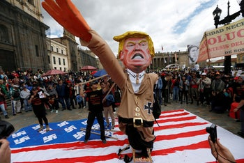 Protesters carry a cutout depicting U.S. President Donald Trump, wearing a Nazi uniform, during a rally commemorating May Day in Bogota, Colombia May 1, 2018.
