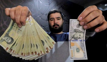 FILE PHOTO: A Money changer poses for the camera with a U.S dollar (R) and the amount being given when converting it into Iranian rials (L), at a currency exchange shop in Tehran's business district, Iran, January 20, 2016. REUTERS/Raheb Homavandi/TIMA  ATTENTION EDITORS - THIS IMAGE WAS PROVIDED BY A THIRD PARTY.