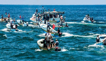 Palestinian activists and fishermen take boats out to sea from the Gaza City port, July 10, 2018.
