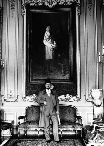 King Farouk of Egypt posing a photograph in front of a portrait of his father, Faud, in May 1944.