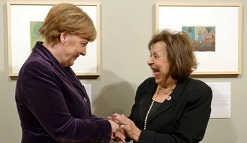 German Chancellor Angela Merkel stands with Holocaust survivor, artist Nelly Toll in Berlin, Germany, January 25, 2016.
