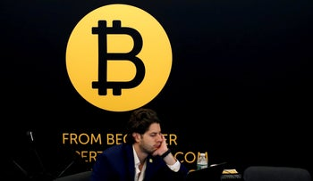 A man works on a laptop beneath the Bitcoin logo at the Consensus 2018 blockchain technology conference in New York City, New York, U.S., May 16, 2018.