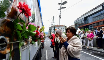 Bosnian Muslims pray near a truck, carrying the remains of 35 newly identified victims of Srebrenica massacre on July 9, 2018.