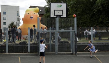 Children playing basketball as a 6-meter (20-foot) cartoon baby blimp of U.S. President Donald Trump stands inflated in north London, July 10, 2018.