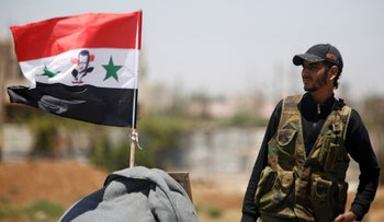 A Syrian army soldier stands next to a Syrian flag in Umm al-Mayazen, in the countryside of Deraa, Syria, July 10, 2018.