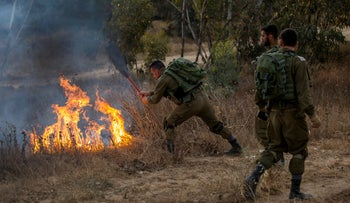 In this Friday, June 1, 2018 file photo, an Israel soldier extinguishes a fire started by a kite with attached burning cloth launched by Palestinians from Gaza, near the Israel Gaza border.