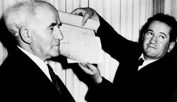 In this May 15, 1948 file photo, David Ben-Gurion, Israel's New Premier, stands with an Israeli official who holds the signed document which proclaims the Establishment of the Jewish State of Israel.