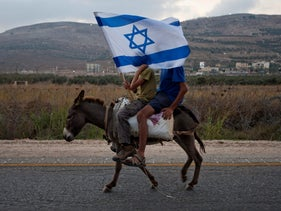 Young settlers riding on a donkey with an Israeli flag as they join a march against Palestinian statehood at Itamar near Nablus, September 20, 2011.