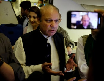 Ousted Pakistani Prime Minister Nawaz Sharif gestures as he boards a Lahore-bound flight due for departure, at Abu Dhabi International Airport, UAE July 13, 2018