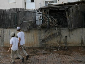 Young residents of the southern Israeli city of Sderot walk in front of a fence damaged by a rocket, July 14, 2018.