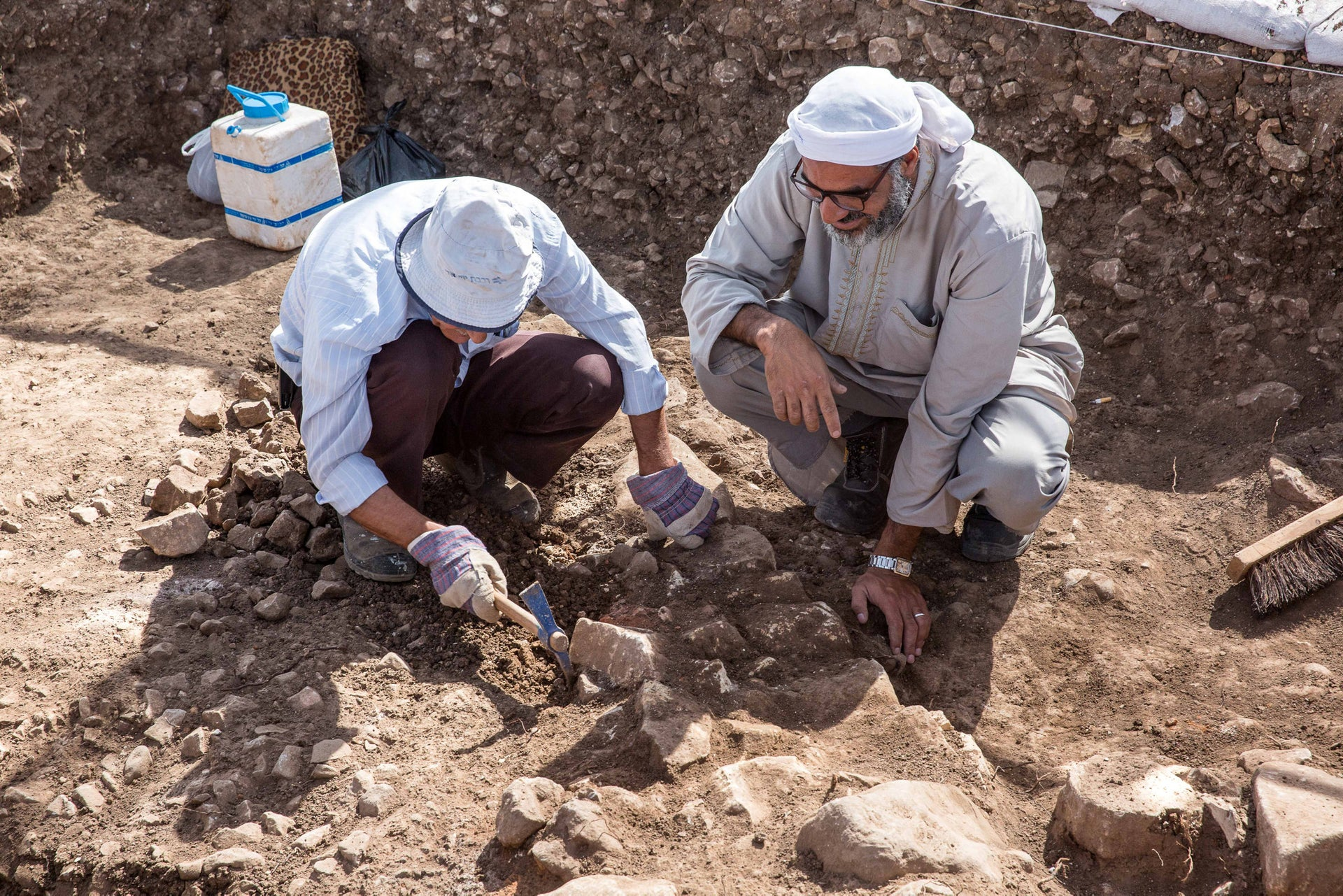Archaeological dig at Motza: 9,000-year-old Neolithic village. Photo shows two men wearing hats against the heat, digging.