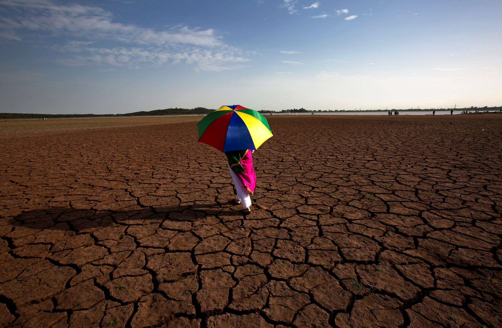 A Pakistani woman walks on a dry bank that provides water to Islamabad and Rawalpindi cities, at Rawal dam in Islamabad, Pakistan, Friday, June 22, 2018. The water level in dams and rivers are low due to dry and hot weather causing water and energy shortage to civilians.
