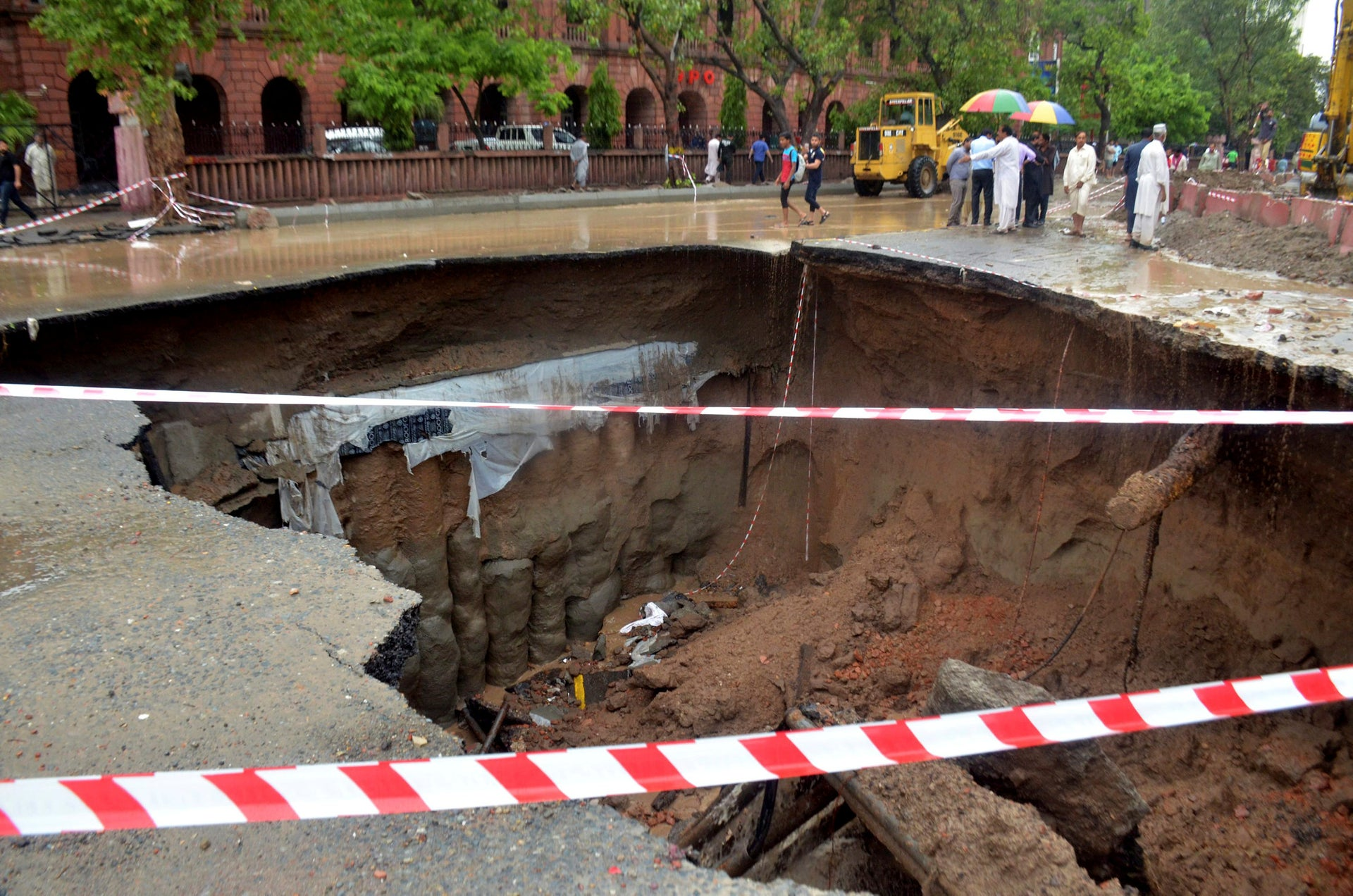 Residents look at a road caved in due to heavy rain fall in Lahore, Pakistan, Tuesday, July 3, 2018. Torrential monsoon rains lashed many cities and towns across Pakistan before dawn Tuesday, flooding streets and killing six people, as authorities struggled to restore normalcy in rain-affected areas.