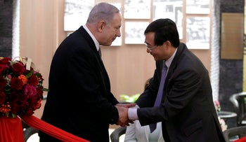 Israeli Prime Minister Benjamin Netanyahu and a local Chinese official shake hands at the Shanghai Jewish Refugees Museum in Shanghai, China, May 7, 2013.