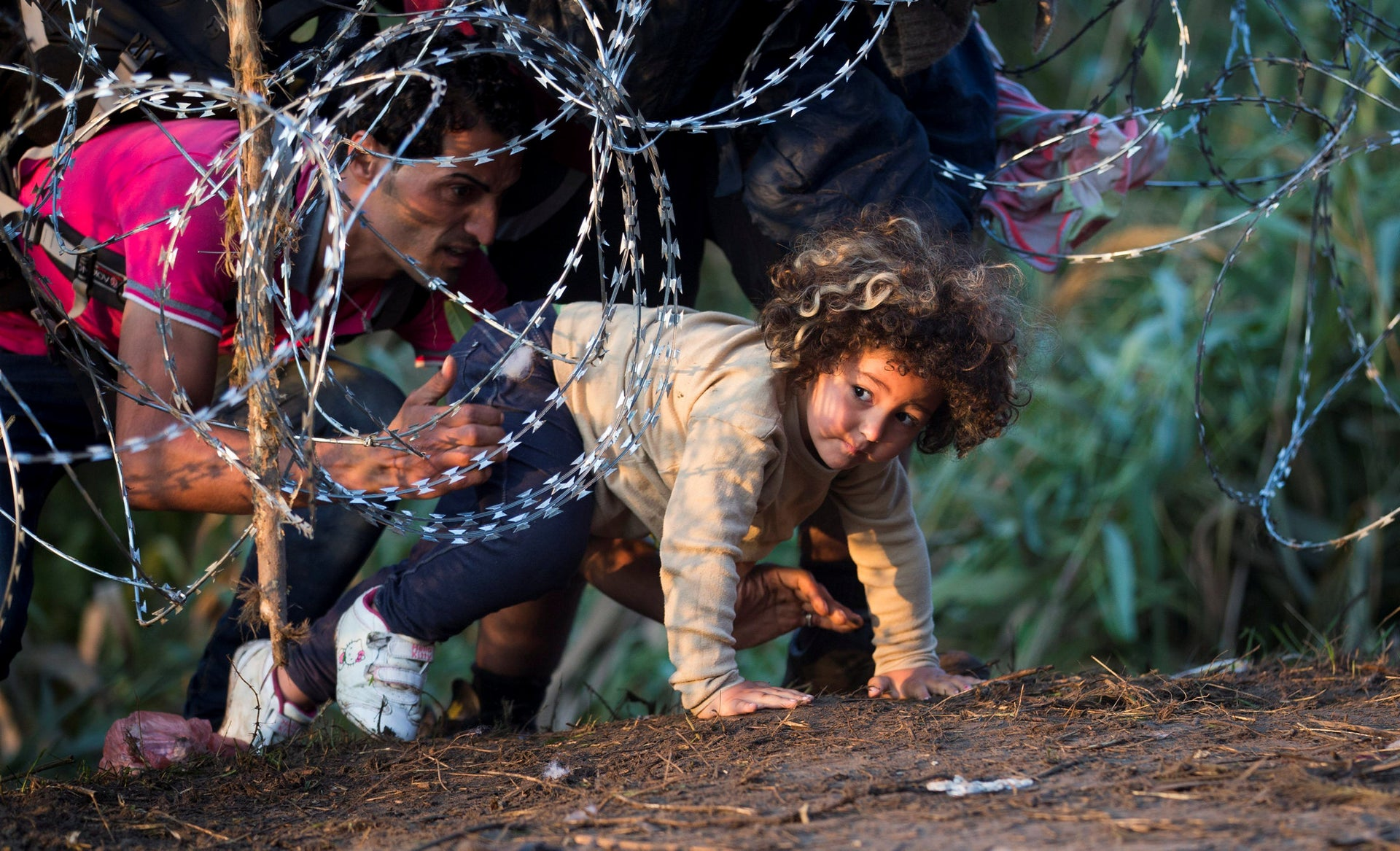 FILE - In this Thursday, Aug. 27, 2015 file photo, a child is helped cross from Serbia to Hungary through the barbed wire fence near Roszke, southern Hungary.