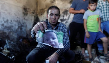 Relative holds a photo of a baby killed in a 2015 arson attack by Jewish terrorists in Douma, along with his parents.