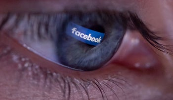 An illustration picture shows a person posing during a photo session showing the social platform Facebook logo reflected in the pupil of an eye on April 25, 2018, in Paris.