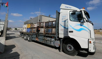 A Palestinian man rides on a truck carrying fruits as it arrives at Kerem Shalom crossing in Rafah in the southern Gaza Strip July 10, 2018.